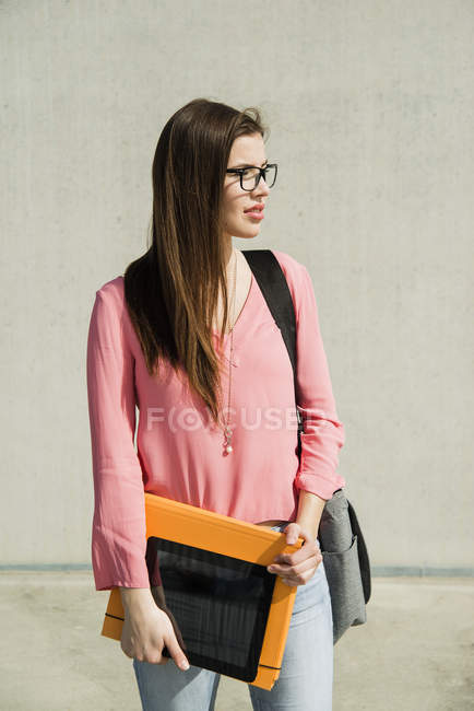 Mujer joven morena con bolsa, carpeta y tableta digital al aire libre - foto de stock