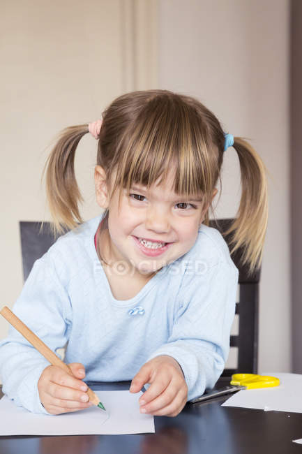 Portrait of smiling little girl drawing with green crayon — Stock Photo