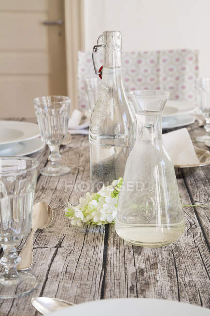 Water bottle, carafe, glasses and white blossom on festive laid table — Stock Photo