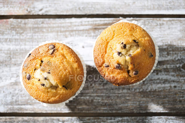 Vue de deux muffins dans des gobelets en papier sur la table en bois gris — Photo de stock