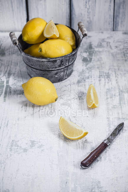 Zitronenschale mit Scheiben und Messer auf schäbigem Holztisch — Stockfoto