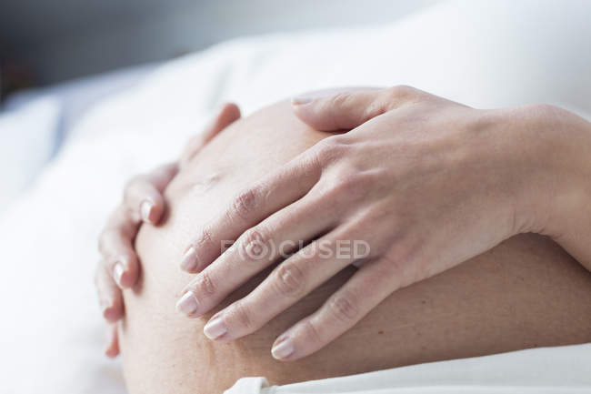Germany, Munich, hands and pregnant belly — Stock Photo