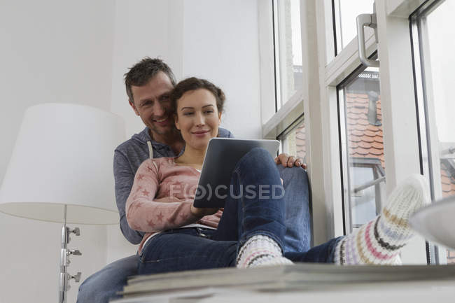Пара, сидячи на підвіконні, за допомогою планшетного комп'ютера — стокове фото