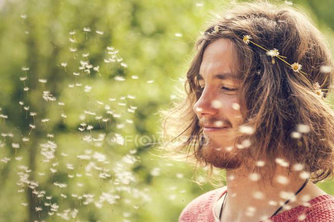 Улыбающийся молодой человек с мячом в природе — стоковое фото