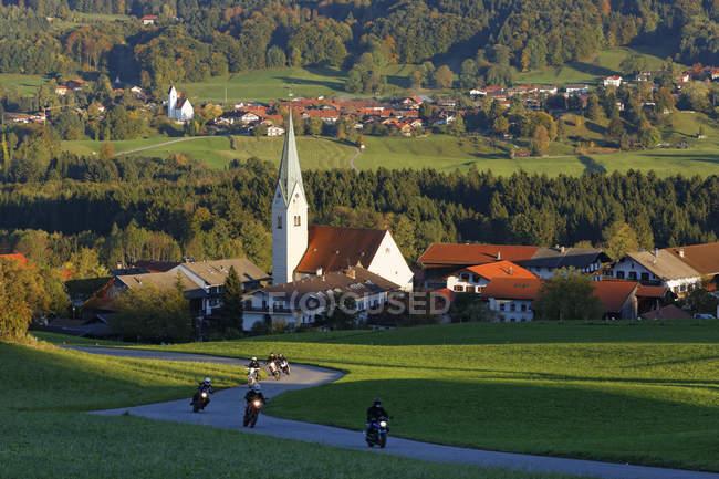 Germany, Bavaria, Chiemgau, bikers driving on country road through Samerberg — Stock Photo