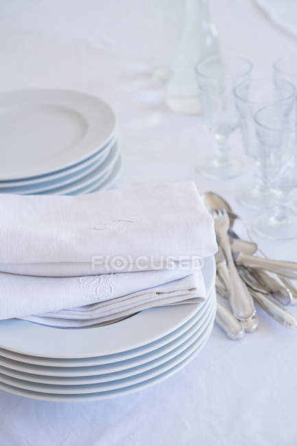 Closeup of glasses, stack of plates, silver cutlery and cloth napkins on white table cloth — Stock Photo