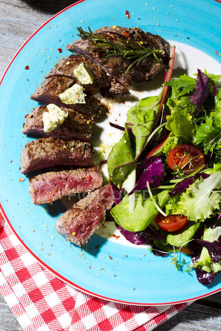 Beef sirloin steak with rosemary, garlic, herb butter, pepper and salad on blue plate over towel — Stock Photo