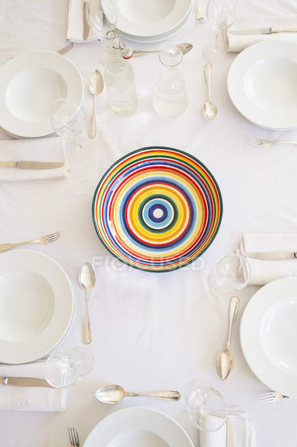 Laid table with colorful bowl in center — Stock Photo