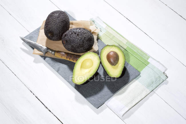 Halved and whole avocados with knife and slate on white wooden table — Stock Photo