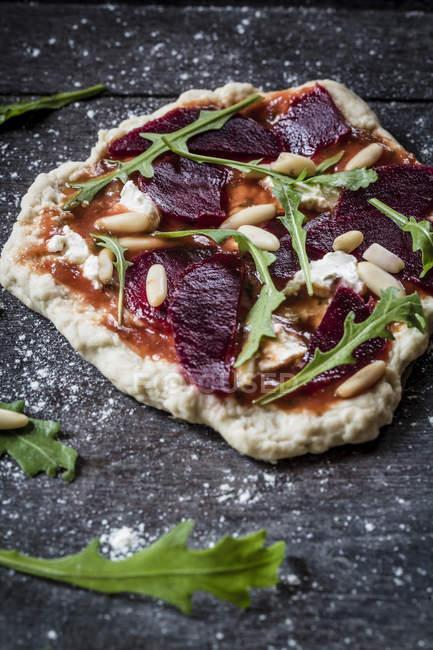 Міні піца з буряк, руколою і кедровими горішками на темні поверхні — стокове фото