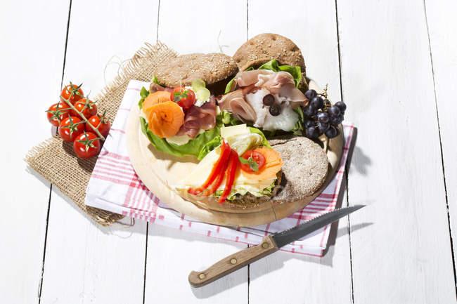 Органическая ржаная булочка с ветчиной, сыром, виноградом и помидорами на белой деревянной поверхности — стоковое фото