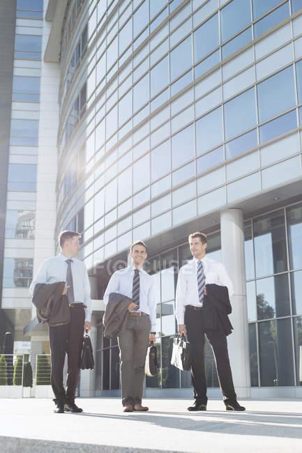 Hommes d'affaires marchant devant l'immeuble de bureaux — Photo de stock