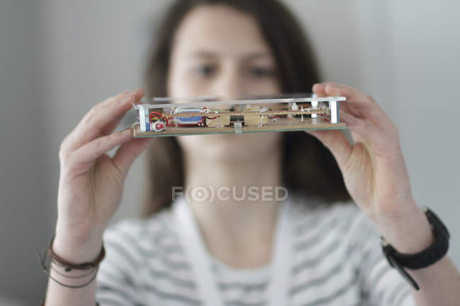 Young woman holding an optical sensor in an electronic workshop — Stock Photo