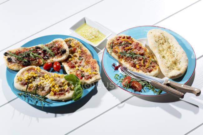 Pizzas with ham, salami, mozzarella, tomato, arugula, maize and olives on white wood — Stock Photo