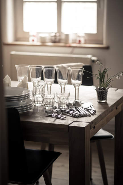 Platos y vasos sobre mesa de madera en cocina - foto de stock