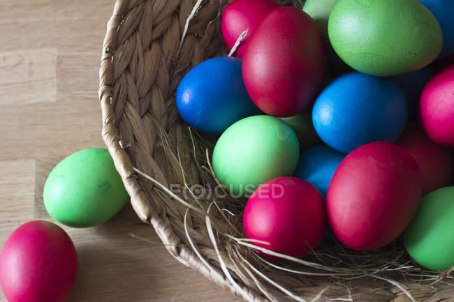 Cesta de ovos de Páscoa coloridos pintados sobre madeira — Fotografia de Stock