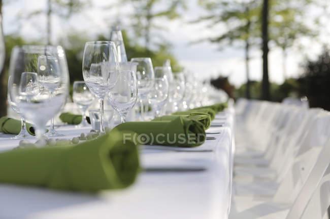 Primo piano di festosa di cui tabella con verde tovaglioli e bicchieri di vino — Foto stock
