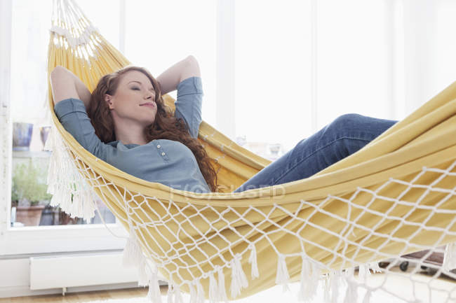 Woman relaxing in a hammock in her apartment — Stock Photo