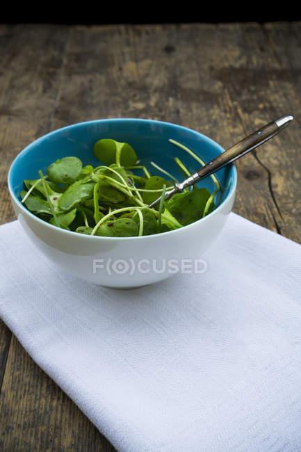 Schüssel mit Winterportulak-Salat auf weißem Tuch auf Holztisch — Stockfoto