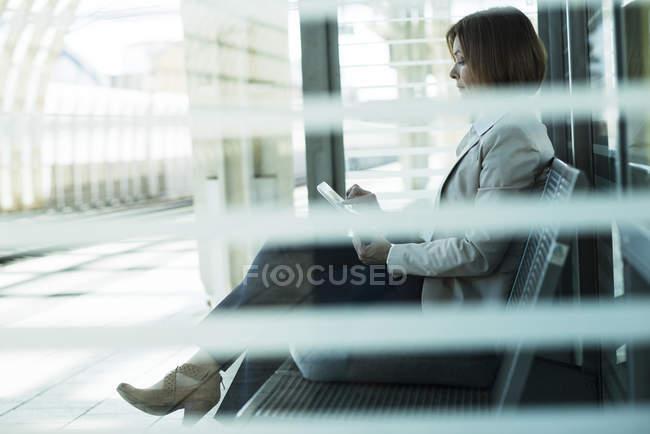 Donna d'affari utilizzando tablet computer in attesa sulla piattaforma — Foto stock