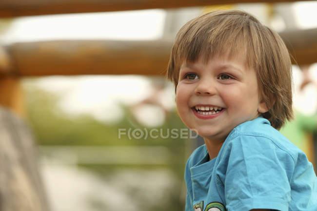 Retrato de um menino sorridente sentado no parque infantil — Fotografia de Stock