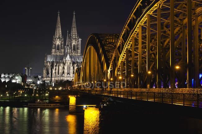Alemania, Renania del Norte-Westfalia, Colonia, Catedral y Puente Hohenhollern sobre el río Rin iluminado de noche - foto de stock