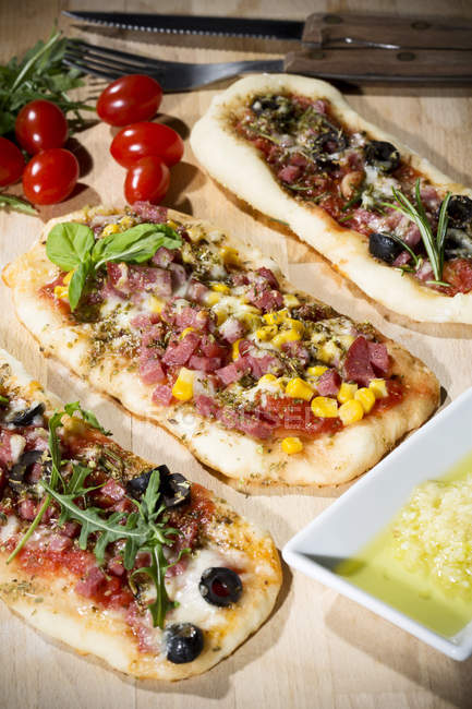 Pizzas with ham, salami, mozzarella, tomato, arugula, maize and olives on wood — Stock Photo