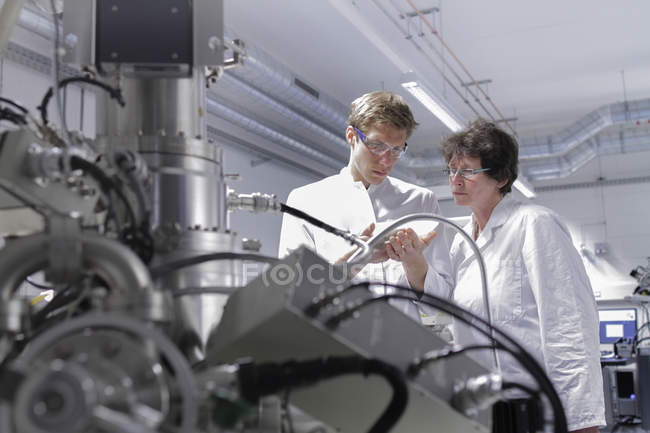 Two scientists standing in analytical laboratory with scanning electron microscope in foreground — Stock Photo