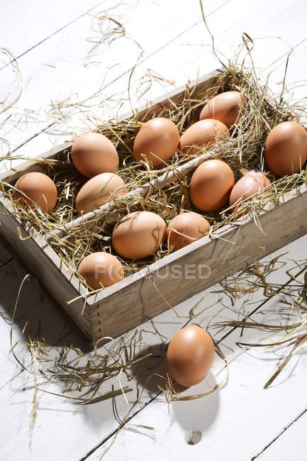 Closeup of wooden box of brown eggs and hay on white wooden table — Stock Photo