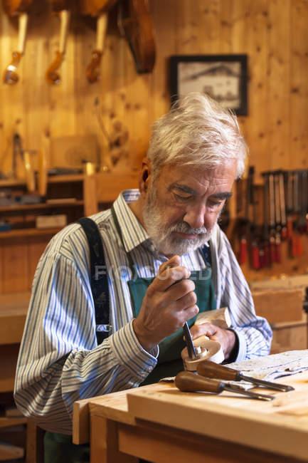 Closeup view of senior caucasian violin maker at work in workshop — Stock Photo