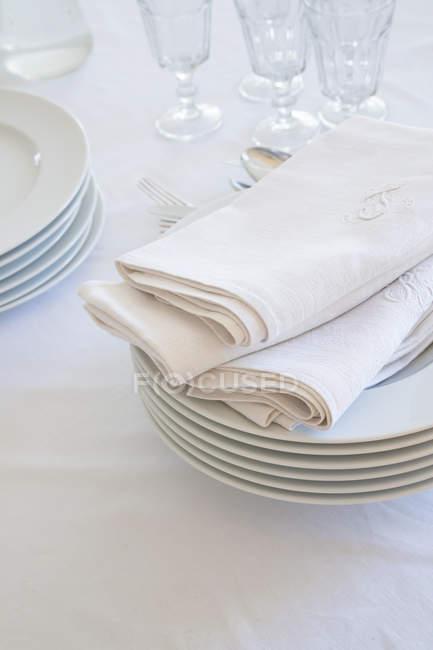 Primer plano de vasos, pila de platos y servilletas de tela en manteles blancos - foto de stock