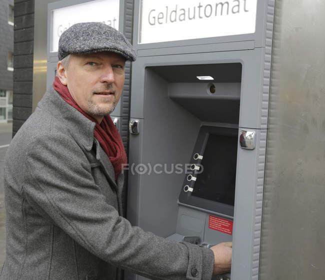 Homme debout au distributeur de billets — Photo de stock