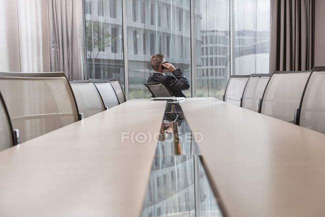 Businessman telephoning while looking out of window — Stock Photo