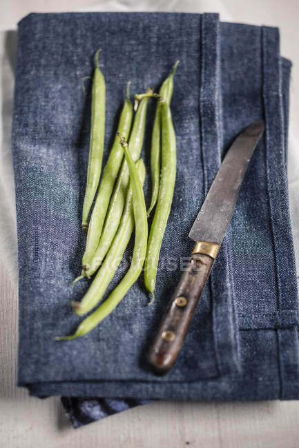Green beans on blue kitchen towel with knife — Stock Photo