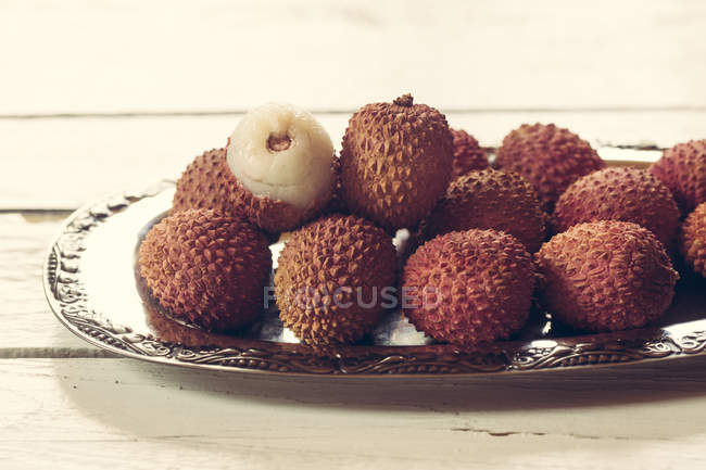 Silver plate of whole lychees with half on wooden table — Stock Photo