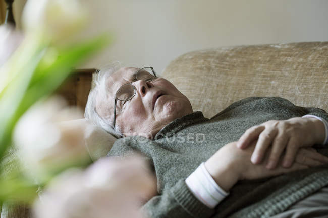 Senior man having midday sleep on sofa — Stock Photo