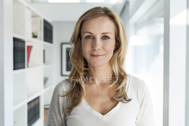 Portrait of woman standing in modern home and looking at camera — Stock Photo