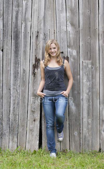 Jeune femme se penchant à une façade en bois grise — Photo de stock