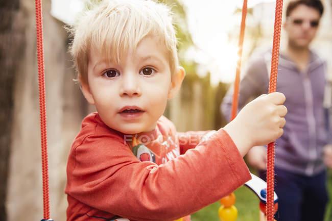 Portrait du petit garçon sur une balançoire — Photo de stock