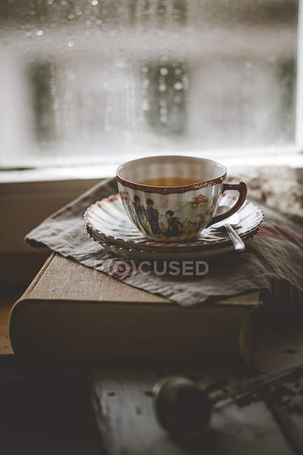 Cup of Chinese green jasmin tea on book — Stock Photo