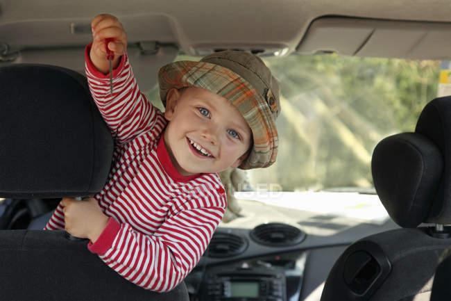 Ragazzino mostrando cacciavite in macchina — Foto stock