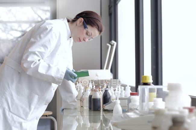 Jeune scientifique au travail en laboratoire — Photo de stock