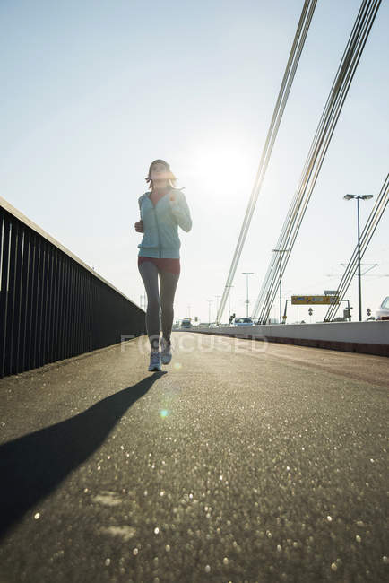 Young female jogger on the move on a bridge — Stock Photo