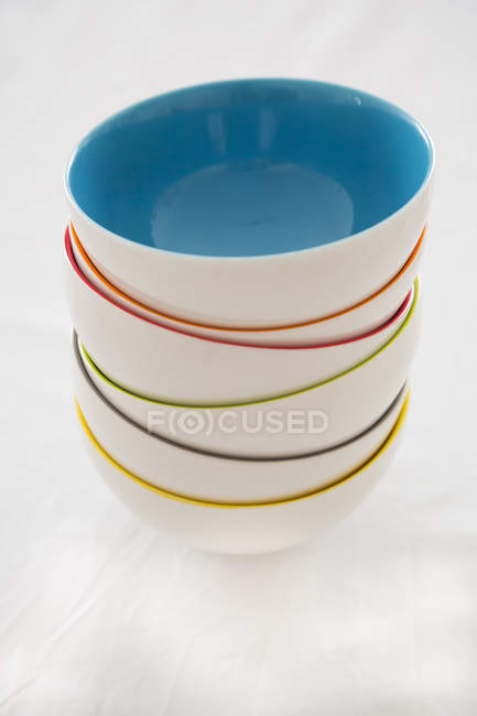 Stack of six coloured bowls on white background — Stock Photo
