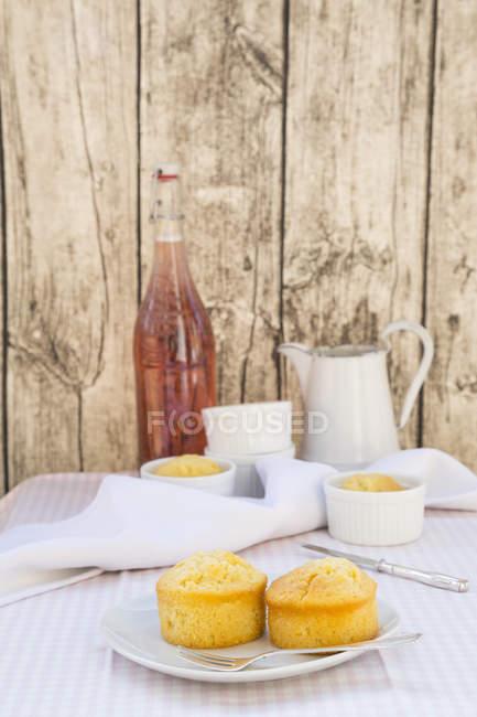 Кастрюли с яблочными пирогами, банка и бутылка ревеневого сока на ткани перед деревянной стеной — стоковое фото