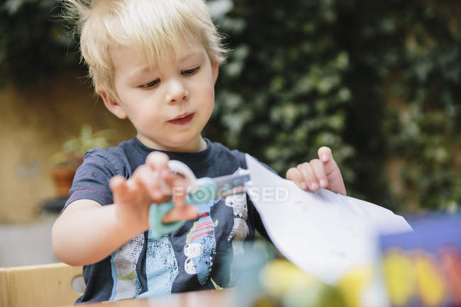 Ritratto di piccolo ragazzo che taglia carta con le forbici dei bambini — Foto stock