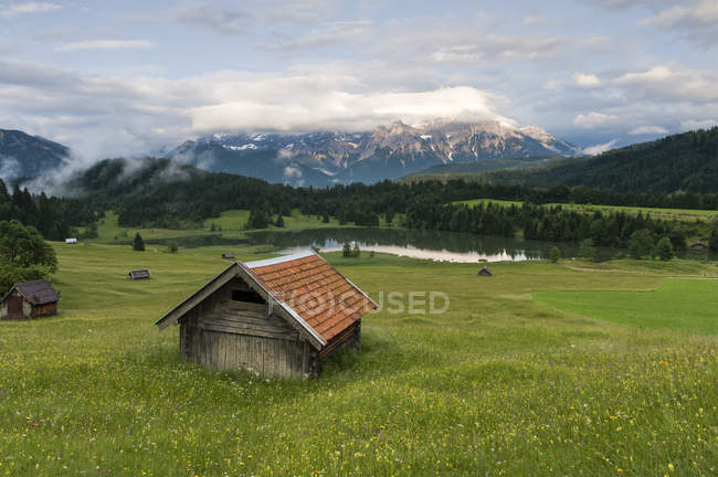 Germany, Bavaria, Werdenfelser Land, lake Geroldsee with hay barn at sunset, in background the Karwendel mountains — Stock Photo
