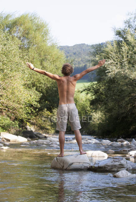 Austria, Salzkammergut, Mondsee, young man with outstretched arms standing at a brook — Stock Photo