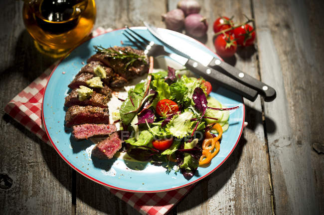 Beef sirloin steak with rosemary, garlic, herb butter, pepper and salad over wooden surface — Stock Photo