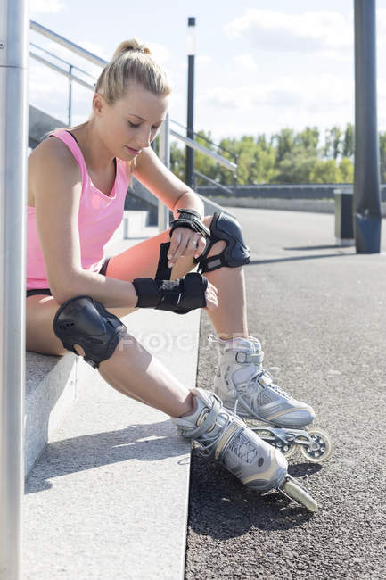 Young woman wearing in-line skates sitting on stairs in city — Stock Photo